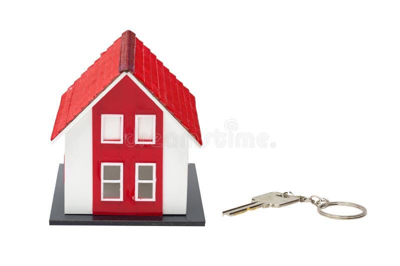 Rotes Hausmodell und Hausschlüssel lokalisiert auf weißem Hintergrund stockfoto
