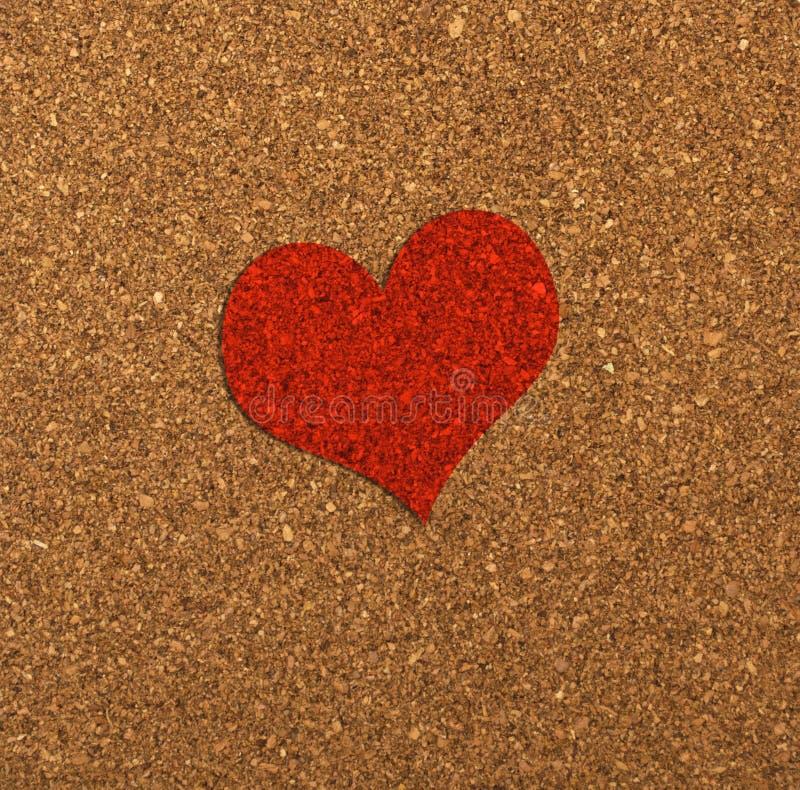 Rotes Herz auf einem Korkenbrett. stockfotos