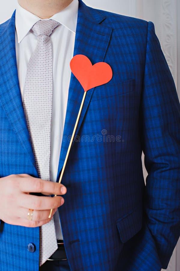 Rotes Herz auf einem Stock in den Händen eines Mannes lizenzfreie stockfotografie