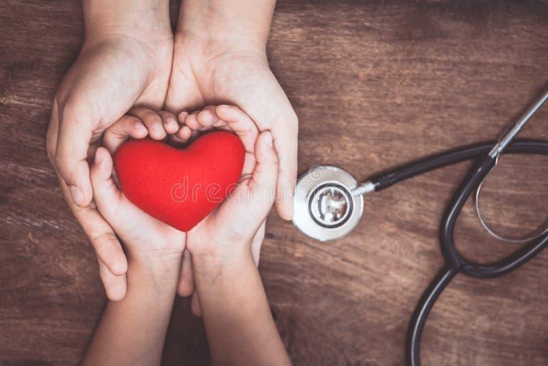 Rotes Herz auf Frauen- und Kinderhänden und mit Doktor ` s Stethoskop lizenzfreie stockfotos