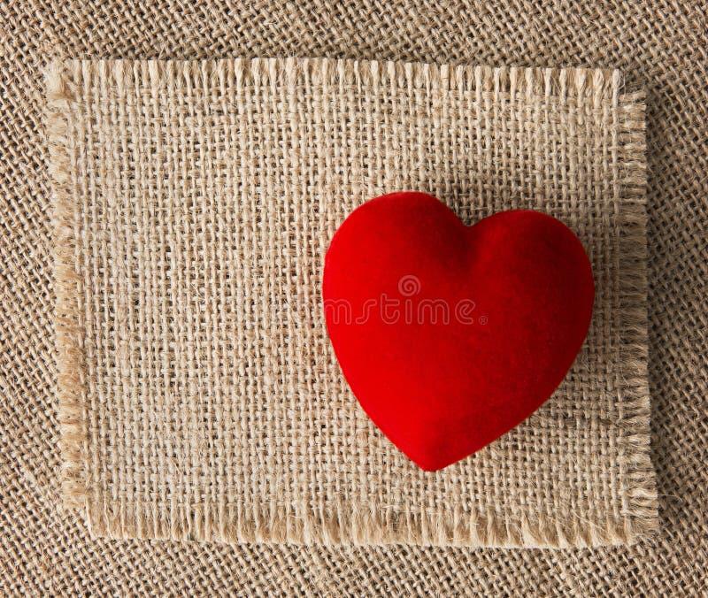 Rotes Herz auf Leinwand, Sackleinenhintergrund Rote Rose stockbild