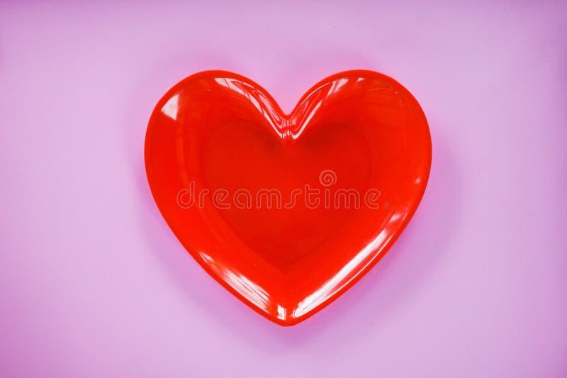 Rotes Herz auf rosa/romantischem Liebeskonzept des Valentinsgrußabendessens - romantisches Gedeck stockfotos
