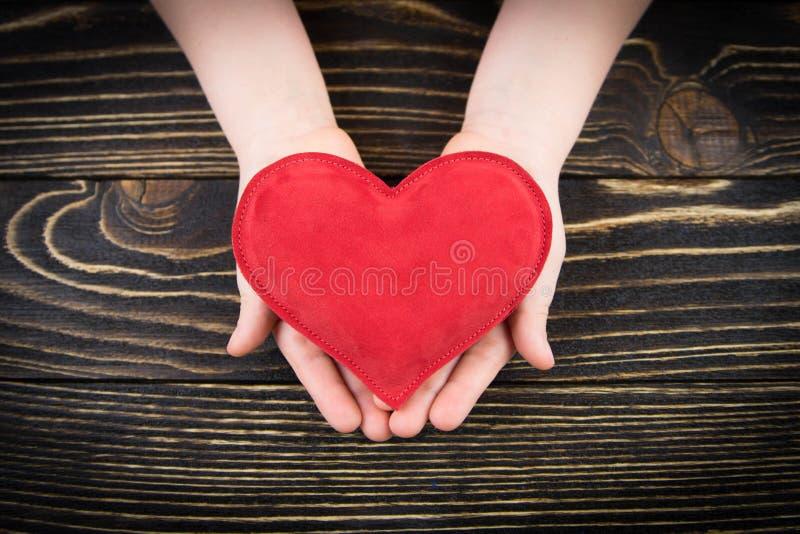 Rotes Herz in den Händen der Kinder lizenzfreies stockbild