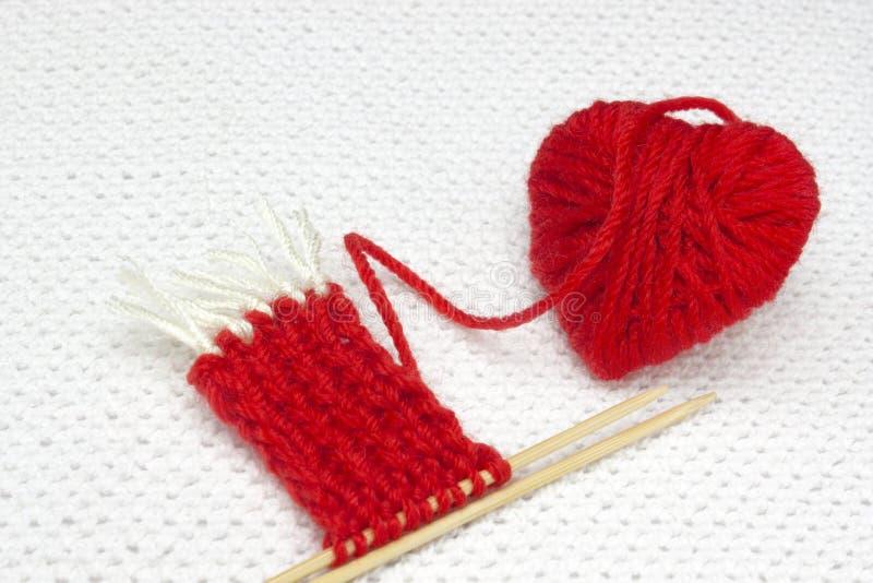 Rotes Herz gemacht vom Wollgarn Roter Garnball wie ein Herz und der Anfang roten Sankt-Schals auf dem weißen Häkelarbeithintergru stockfotos