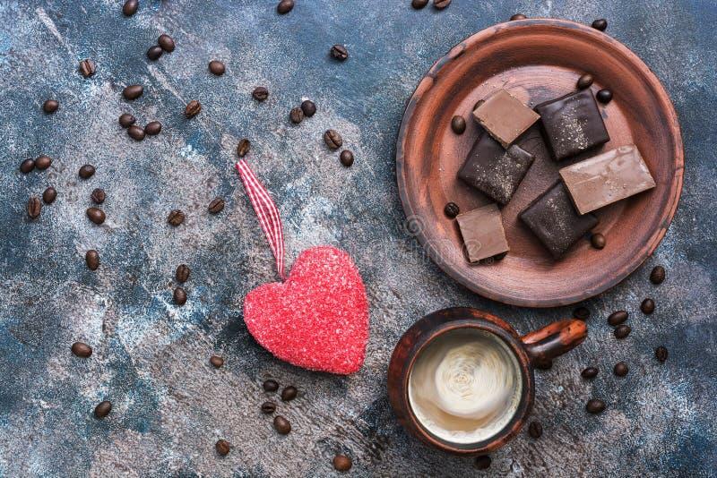Rotes Herz, heißer Kaffee und Praline auf einem rustikalen Hintergrund Valentinsgruß `s Tag Draufsicht, Kopienraum stockbild