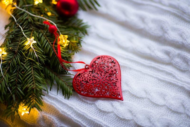 Rotes Herz mit Verzierung nahe dem Tannenkranz verziert mit Weihnachtsbällen und mit glühender Girlande mit warmem Licht auf weiß stockbild