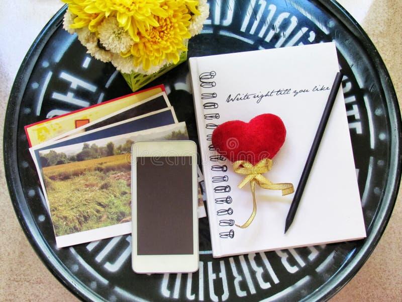 Rotes Herz und Bleistift auf dem Notizbuch, Handy, Fotos macht es eine Postkarte und Blumen auf grüner Stahltabelle tun sie sich  lizenzfreie stockbilder