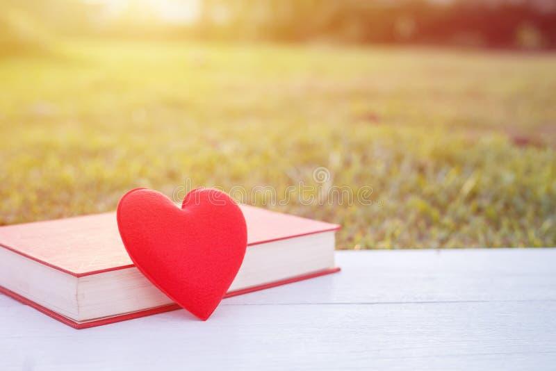 Rotes Herz und Buch auf weißer hölzerner Plattform Für Liebe oder Valentinsgruß d stockbild