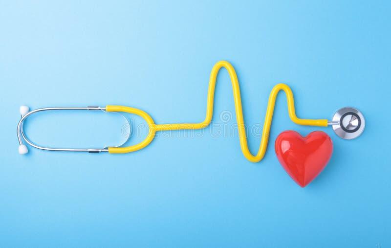 Rotes Herz und ein Stethoskop auf blauem Hintergrund stockfoto