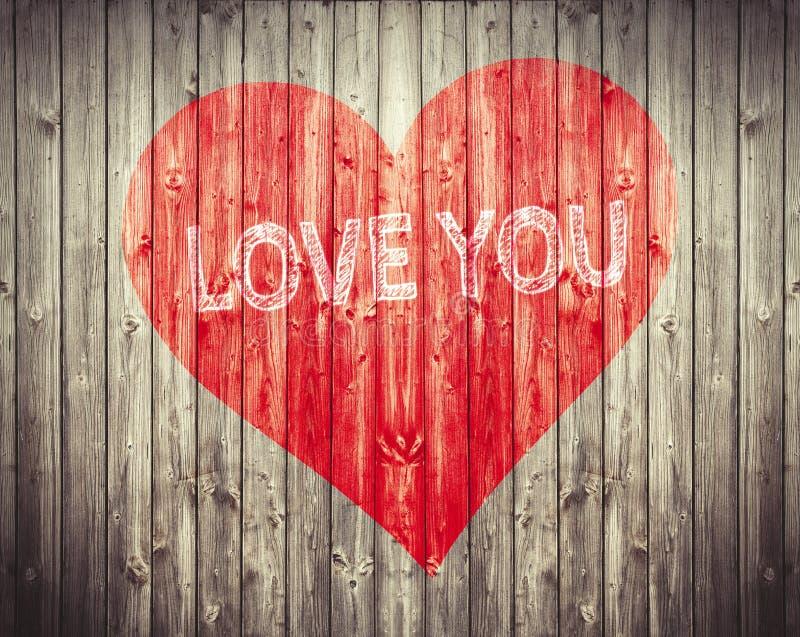 Rotes Herz und lieben Sie Satz auf hölzernem Hintergrund Romantisches Symbol gemalt lizenzfreies stockbild