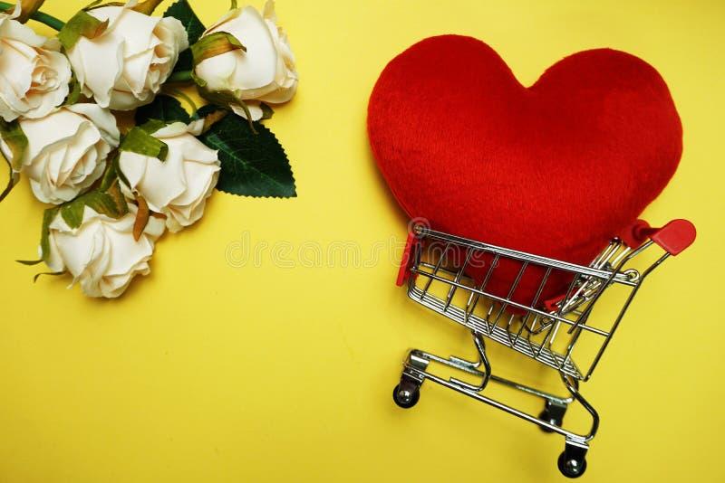 Rotes Herz und Mini-Trolley Einkaufszentrum Gelb Hintergrund lizenzfreies stockfoto