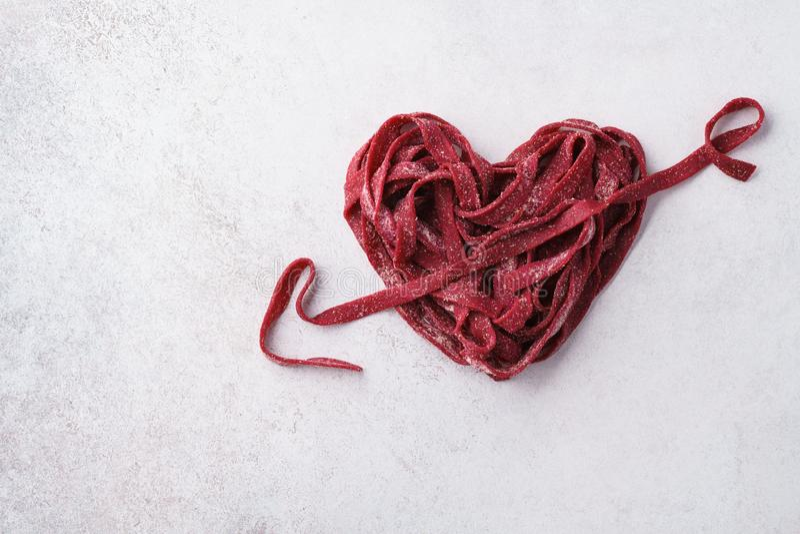 Rotes Herz und Pfeil gemacht von den Teigwaren Rote-Bete-Wurzeln strengen Vegetariers lizenzfreie stockfotografie
