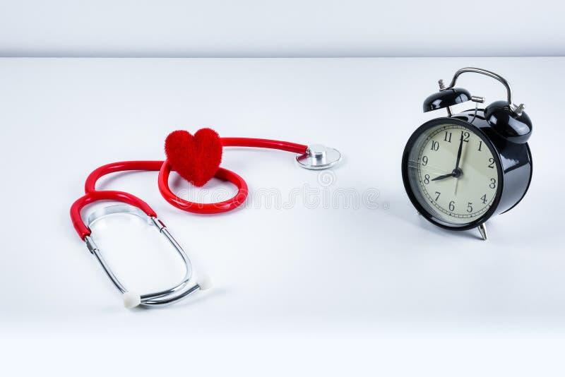 Rotes Herz und Stethoskop, Wecker auf Tabelle lizenzfreie stockfotos