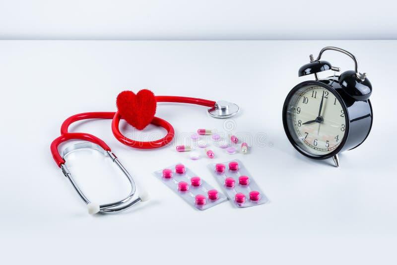 Rotes Herz und Stethoskop, Wecker, Drogen, Pillen auf Tabelle stockfotografie