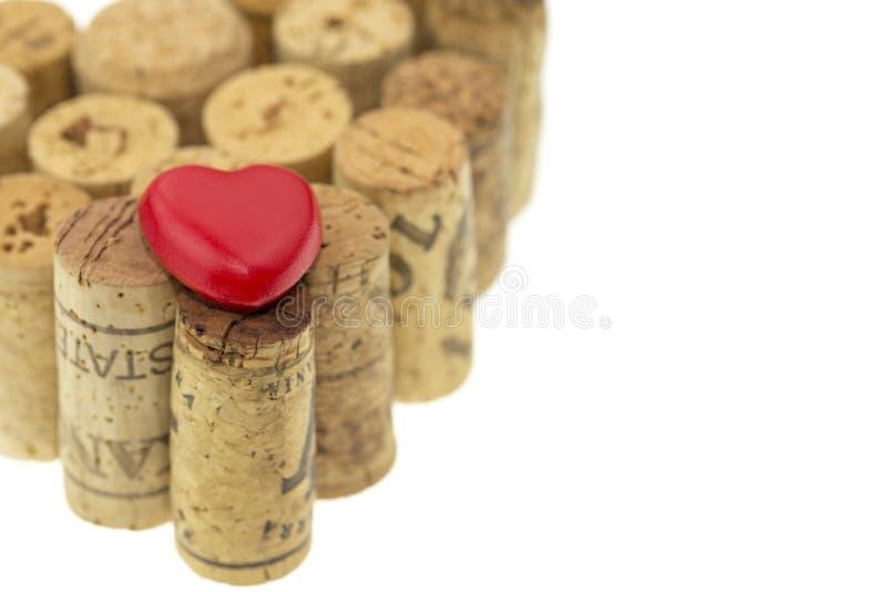 Rotes Herzsymbol auf Wein bekorkt Form, die ein Herzformbild auf Weiß lokalisierte stockfotos