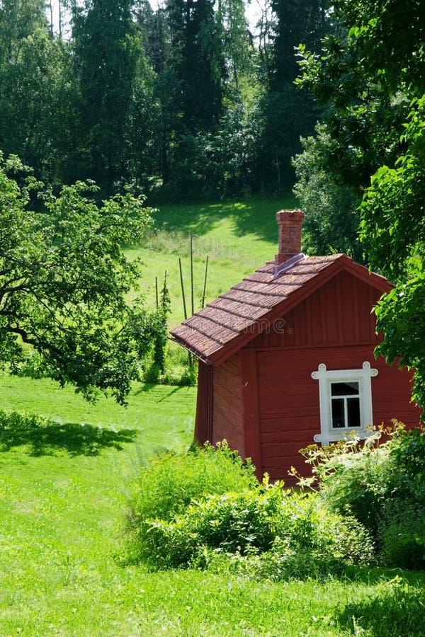 Rotes idyllisches Häuschen in der Sommerlandschaft lizenzfreies stockbild