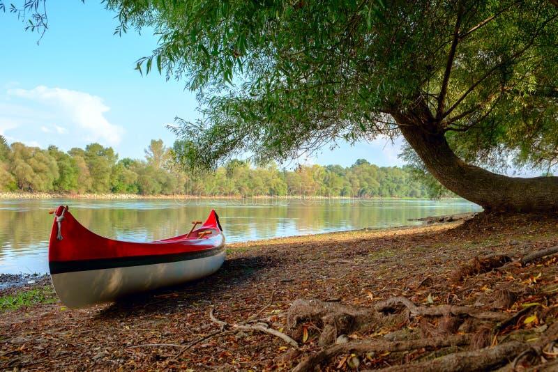 Rotes Kanu auf Strand in Fluss Donau lizenzfreies stockfoto