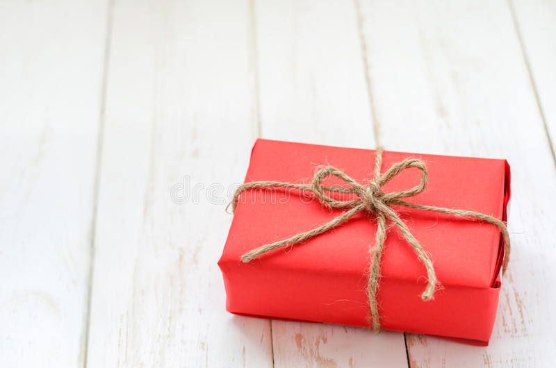Rotes Kastengeschenk auf weißem Holztisch lizenzfreies stockbild
