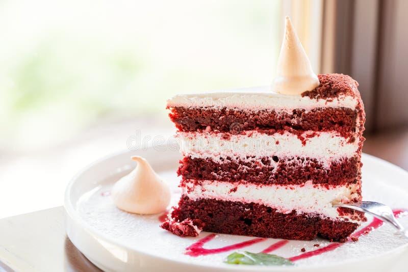 Rotes Kekskuchenstück mit Sahne und Abschluss-nach weißer Platte stauen lizenzfreies stockfoto