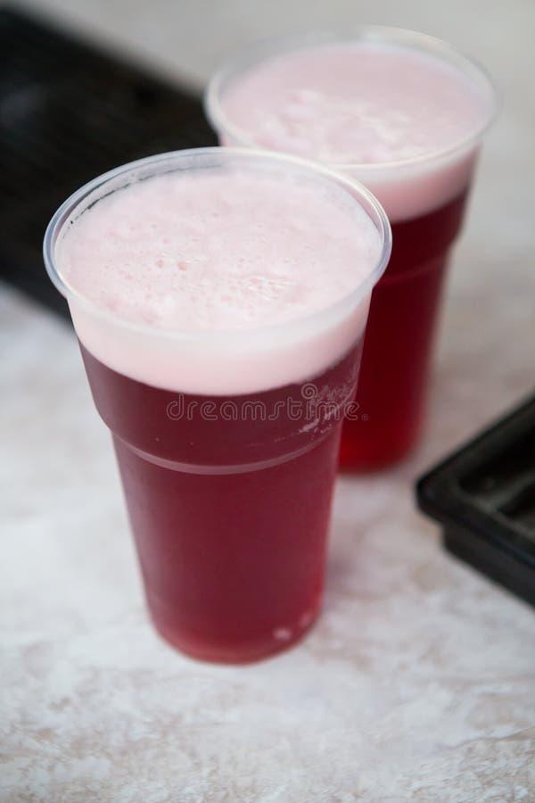 Rotes Kirschbier in Plastikschalen lizenzfreies stockfoto