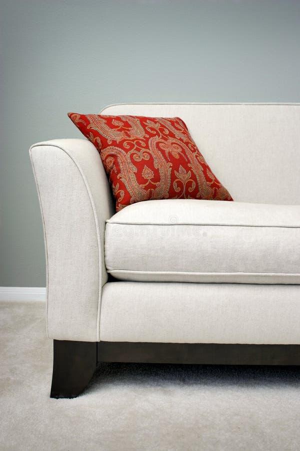 Rotes Kissen auf einem Sofa stockbilder