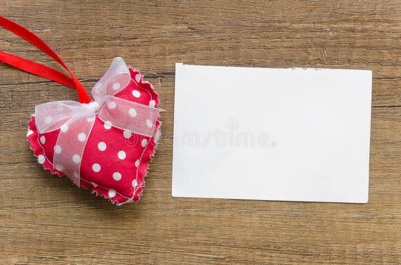 Rotes Kissenherz mit weißen Punkten und einem Bogen und auf hölzernem Hintergrund mit einer leeren Liste für Grußkarte Raum f?r T stockbild