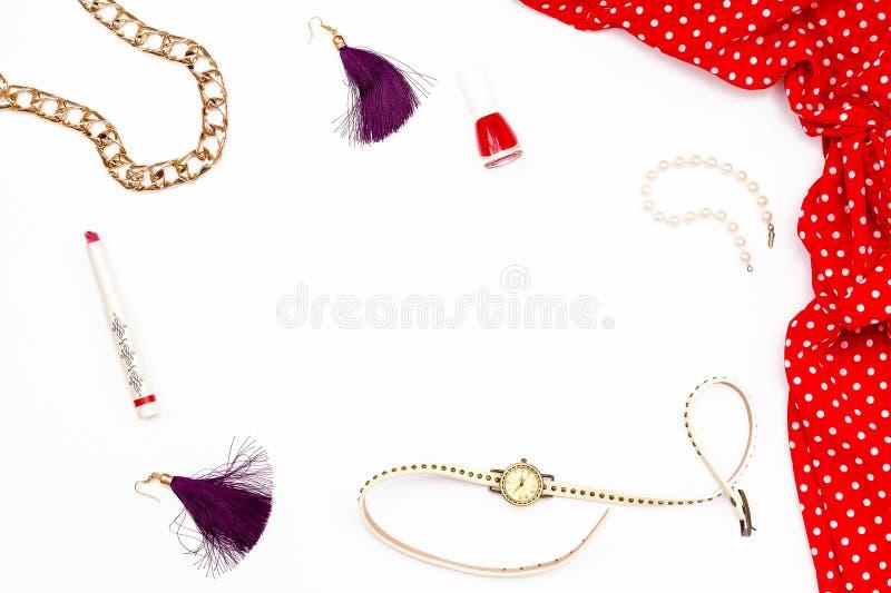 Rotes Kleid, Armband, Lippenstift, Nagellack, Uhren und Ohrringe auf einem weißen Hintergrund Weibliche Schönheit des minimalen K lizenzfreies stockfoto