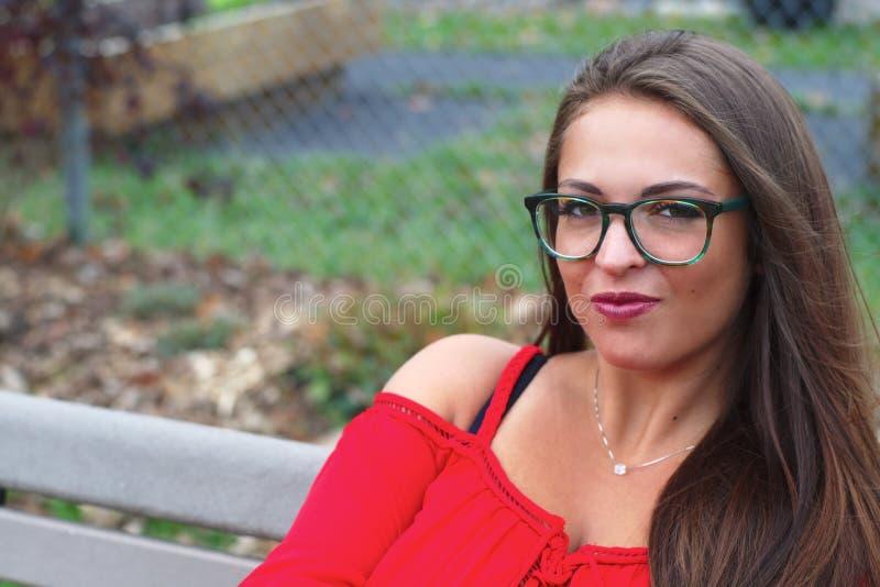 Rotes Kleid junger Dame, das auf einer Bank im Park sitzt stockfotografie