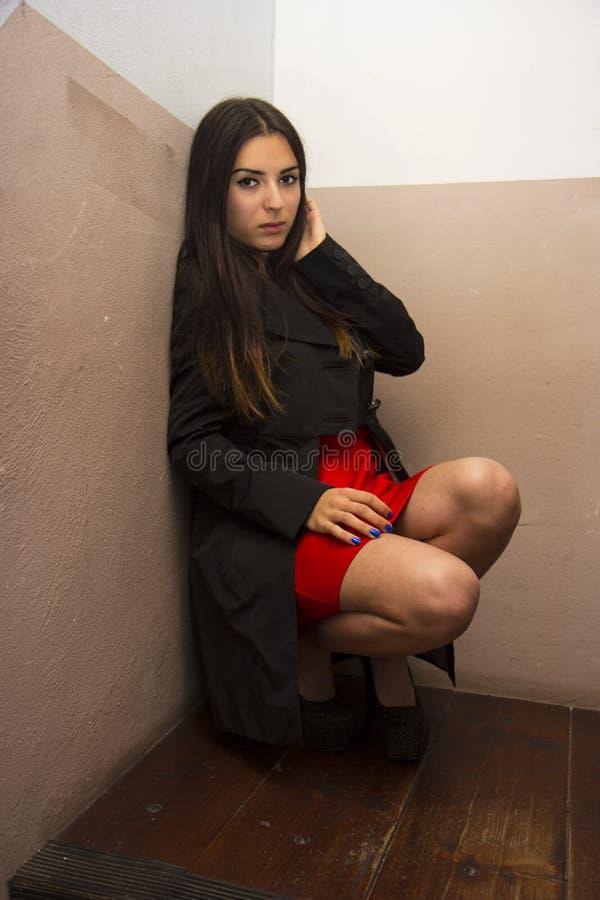 Rotes Kleid u. schwarzer Mantel lizenzfreie stockfotografie
