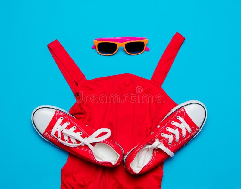 Rotes Kleid und Gummiüberschuhe mit Sonnenbrille lizenzfreie stockfotos