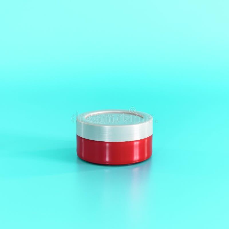 Rotes kosmetisches Glas auf blauem Hintergrund Kopieren Sie Raum für Text stockbild