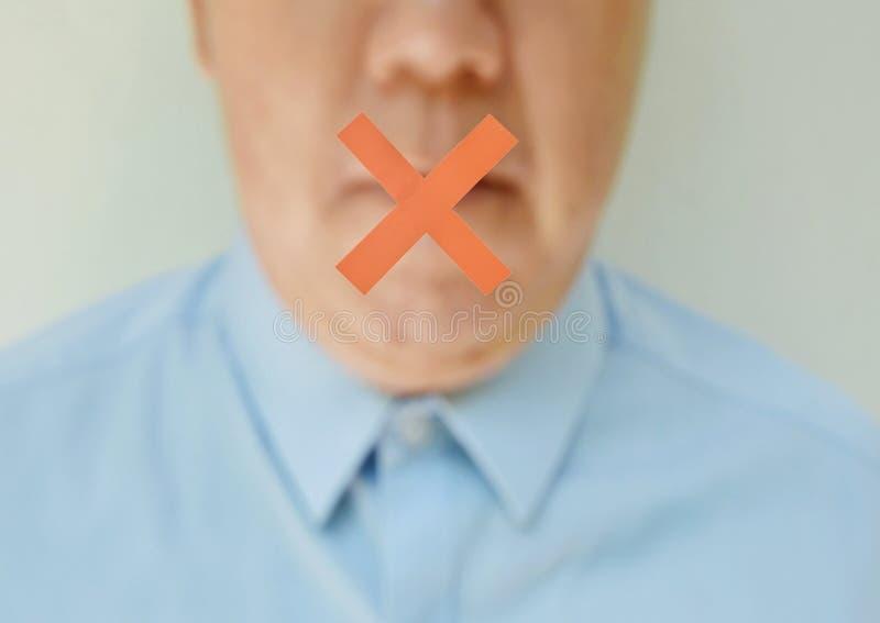 Rotes Kreuz auf Mund des undeutlichen MittelalterGeschäftsmannes im blauen Hemd stockfotografie
