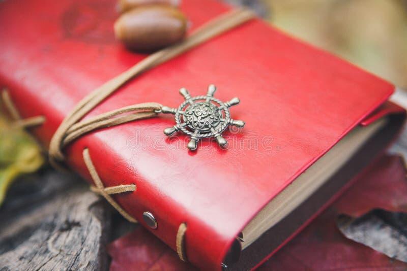 Rotes ledernes Notizbuch mit rundem Stahlzusatz Selektiver Fokus stockbild