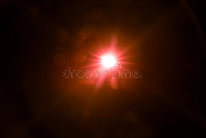 Rotes Licht des Zusammenfassungsblendenflecks über Schwarzem stockbild