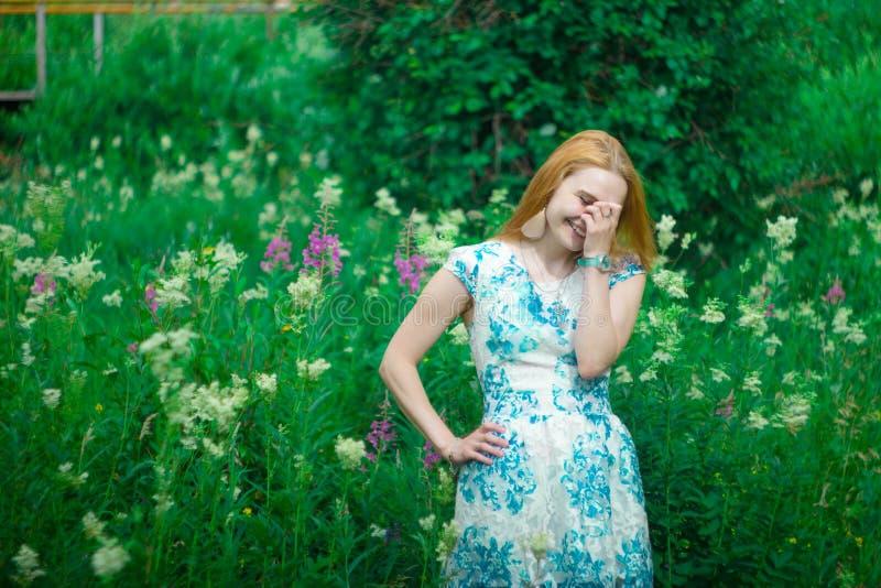 Rotes Mädchen, das auf einer Blumenwiese steht lizenzfreie stockfotografie