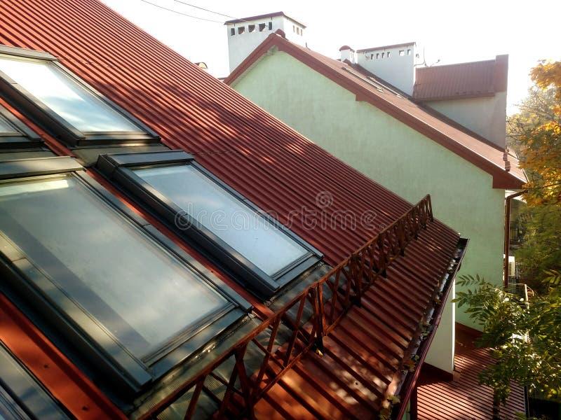 Rotes mit Ziegeln gedecktes Hausdach mit Dachbodenfenstern ?berdachung des Baus, Fensterinstallation, modernes Architekturkonzept lizenzfreie stockbilder