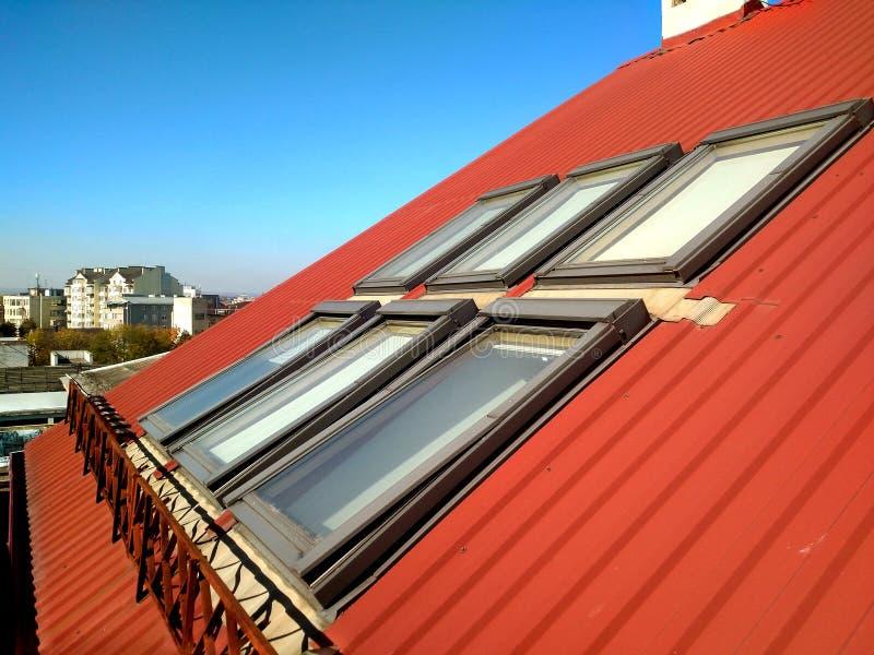 Rotes mit Ziegeln gedecktes Hausdach mit Dachbodenfenstern ?berdachung des Baus, Fensterinstallation, modernes Architekturkonzept stockfoto