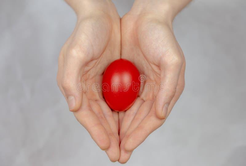 Rotes Osterei, das in seiner Palme, ein religiöses Symbol liegt stockfoto