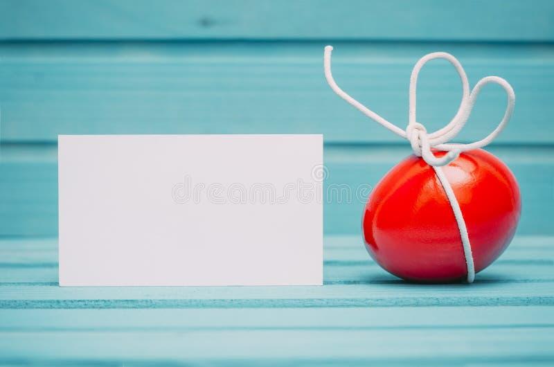 Rotes Osterei mit weißem Bogen auf blauem hölzernem Hintergrund mit leerer Karte lizenzfreies stockbild