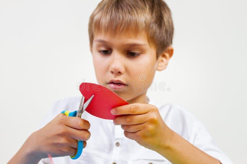 Rotes Papierherz in den Kinderhänden Kind, das rotes Papierherz mit Scheren schneidet lizenzfreie stockfotografie
