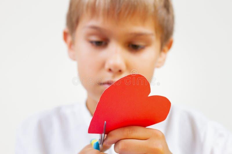 Rotes Papierherz in den Kinderhänden Kind, das rotes Papierherz mit Scheren schneidet lizenzfreie stockbilder