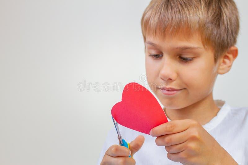 Rotes Papierherz in den Kinderhänden Kind, das rotes Papierherz mit Scheren schneidet stockbilder