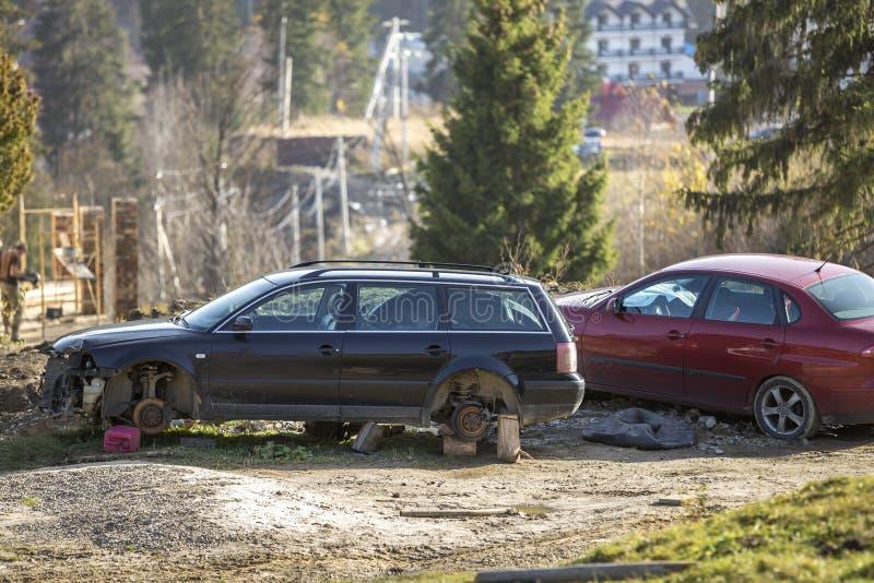 Rotes Parkplatz in der Erholungszone und altes rostiges defektes Abfallauto nach Unglücksfall ohne Räder auf hölzernen Stempeln a lizenzfreie stockfotos