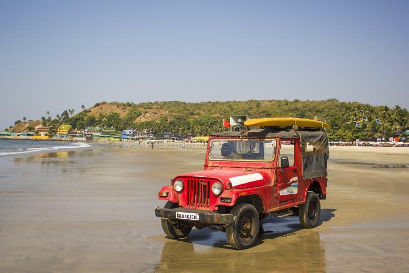 Rotes Rettungsauto mit einem Lautsprecher und einem gelben Brandungsbrett auf dem Dach, auf einem sandigen Strand stockbild