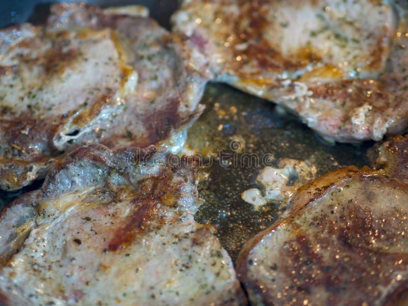 Rotes Rindfleischsteak, das in der Wannengroßaufnahme gekocht wird stockfotos