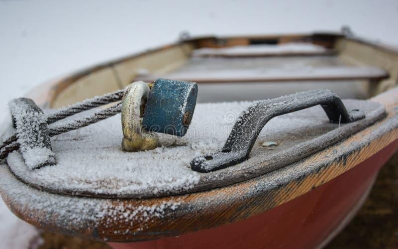 rotes Ruderboot mit blauem Vorhängeschloß füllte mit gefrorenem Wasser lizenzfreie stockbilder