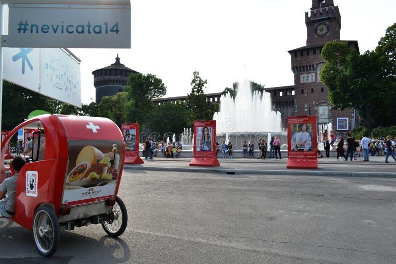 Rotes Schweizer modernes trishaw geparkt auf Rikschastand in Quadrat Castello Sforzesco in Mailand stockbild