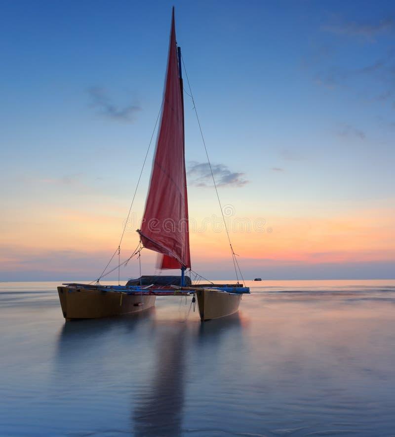 Rotes Segelboot auf dem Strand mit einem schönen Sonnenuntergang stockfotos