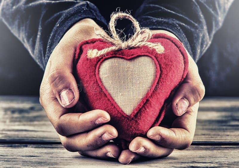 Rotes Segeltuchvalentinsgrußherz in den Händen eines Kindes Herzgeschenk als Zeichen der Liebe stockbild