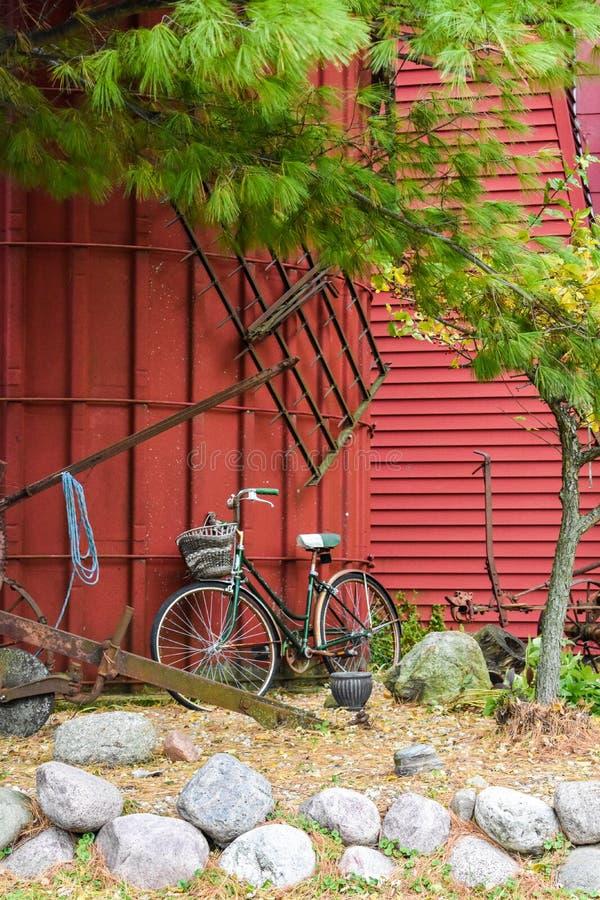 Rotes Silo mit alten Werkzeugen und einem Fahrrad lizenzfreies stockfoto